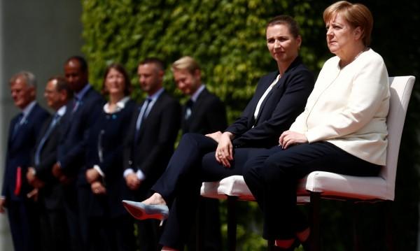 Меркел слуша химна седнала, промениха протокола заради нея