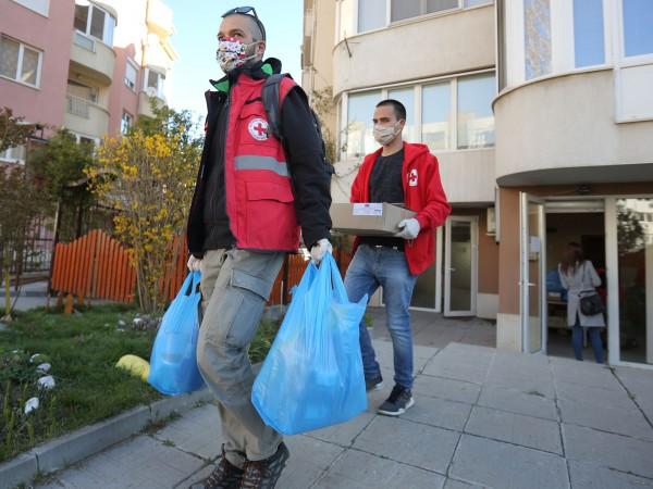 Доброволци на БЧК раздават хранителни пакети на нуждаещи се граждани.Раздаването