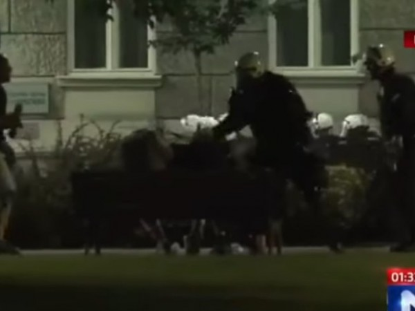Сръбски полицаи удрят трима млади мъже, който седят на пейка