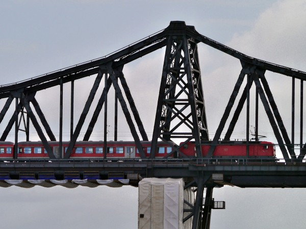Товарен влак се подпали и падна от мост в град