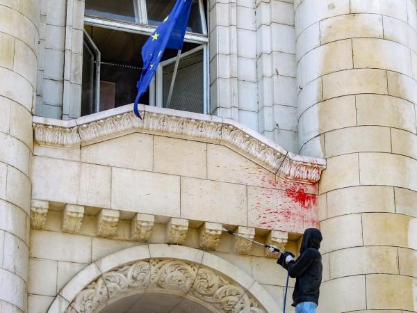 Работници почистват червена боя от фасадата на Съдебната палата, хвърлена