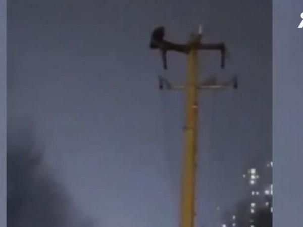 Китаец, провесен върху електрически стълб, за да прави коремни преси,